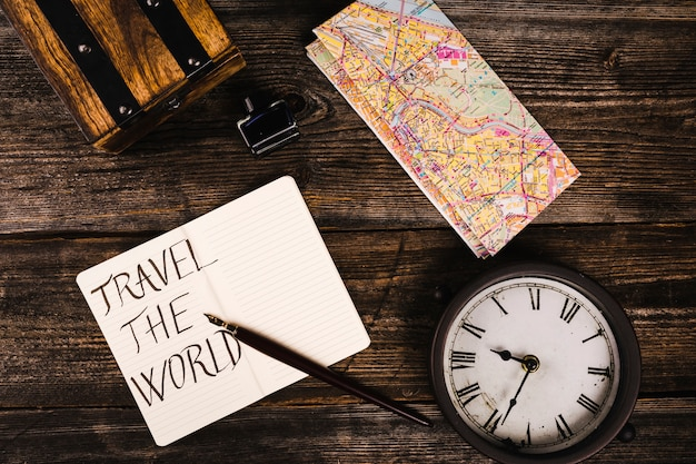 Travel the word text on notepad with map and clock on table