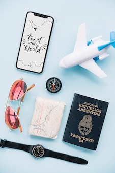 Travel the world message on smartphone with sunglasses; wrist watch; map; passport; compass and toy airplane
