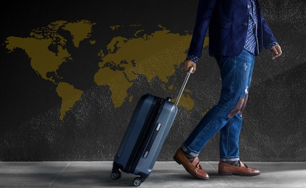 Travel  . young person with luggage walking by the wall. world map