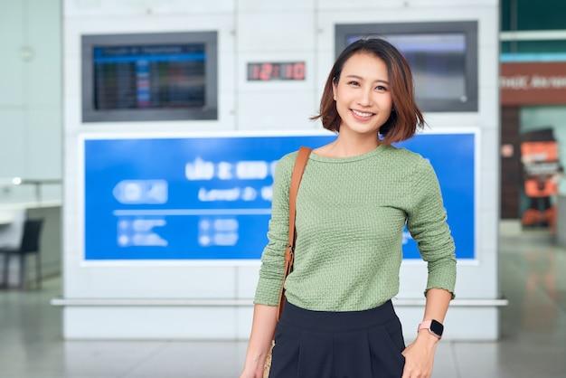 여행하다. 젊은 여성은 비행기를 기다리는 가방을 들고 창가에서 공항으로 간다