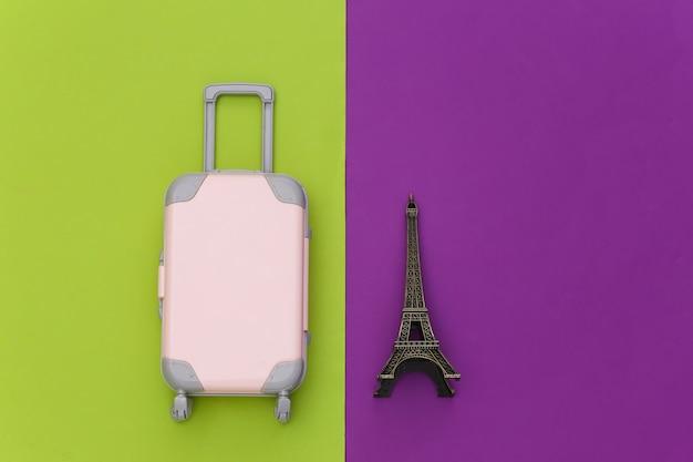 パリに旅行しました。緑紫の背景にエッフェル塔のミニプラスチック製旅行スーツケースと小像。上面図。フラットレイ