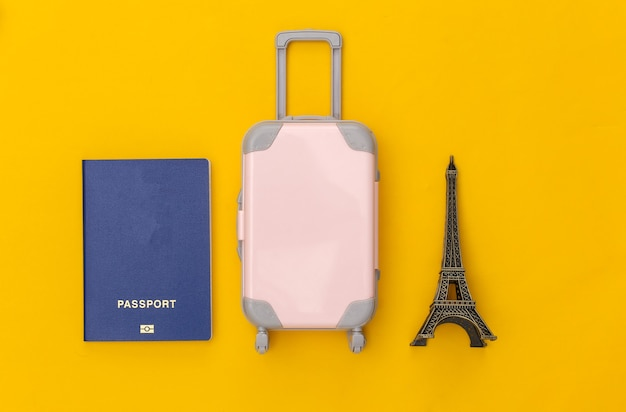 パリに旅行しました。ミニプラスチック製のトラベルスーツケースとエッフェル塔の小像、黄色の背景にパスポート。上面図。フラットレイ