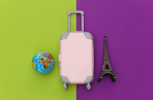 パリに旅行しました。ミニプラスチック製の旅行スーツケース、パスポート、エッフェル塔の小像、緑紫の背景に地球儀。上面図。フラットレイ