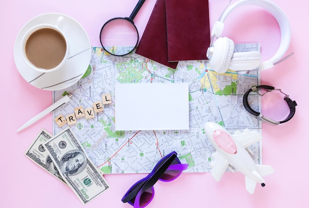 Traveler accessories and cup of tea on pink background