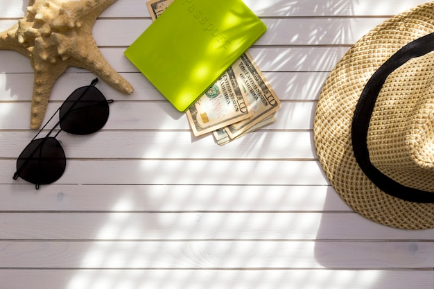 Traveler accessories - passport with cash money us dollars, hat, tropical palm leaf branches shadow.