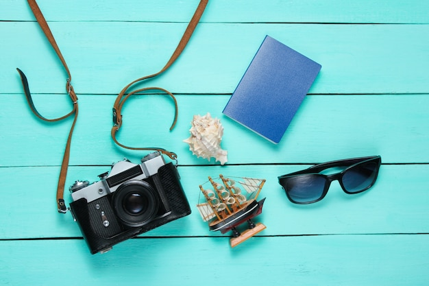 トラベラーアクセサリー、青い木のレトロなカメラ。フラットレイ