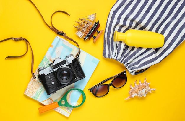 旅行アクセサリー、黄色の背景にレトロなカメラ。ビーチでの旅行、休暇。夏のミニマルな背景。フラット横たわっていた観光の寓話。上面図