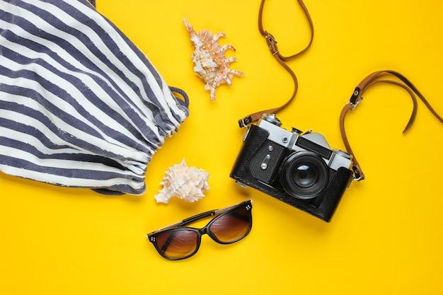 旅行アクセサリー、黄色のレトロなカメラ。フラットレイ