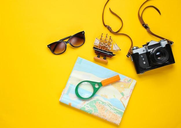 Аксессуары для путешественников, ретро-камера на желтом. плоская планировка