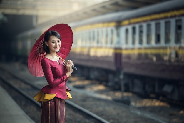 Traveler asia girl wear traditional dress with umbrella waits for train on railway platfor