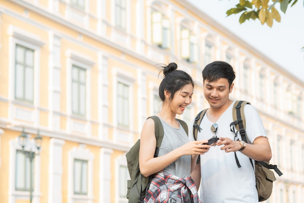 Traveler asian couple direction on location map in bangkok, thailand