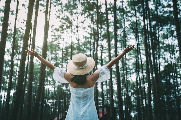 トラベラーアジアの女性がドイボルアンフォレストパークチェンマイタイの松の木の庭で腕を開く