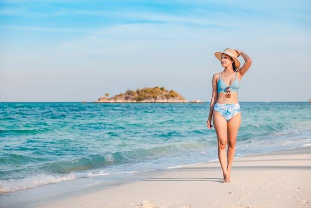 Азиатская женщина-путешественница с бикини и шляпой, расслабляющаяся на морском пляже днем в ко липе, сатун, таиланд