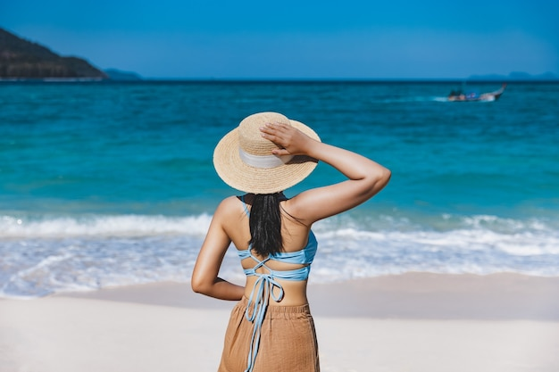 Traveler asian woman with bikini and hat relaxing on sea beach at day in koh lipe, satun, thailand