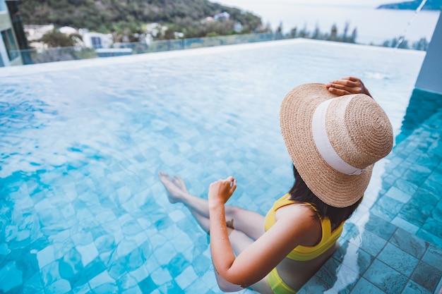 Traveler asian woman with bikini relax in luxury infinity pool resort at day in phuket thailand
