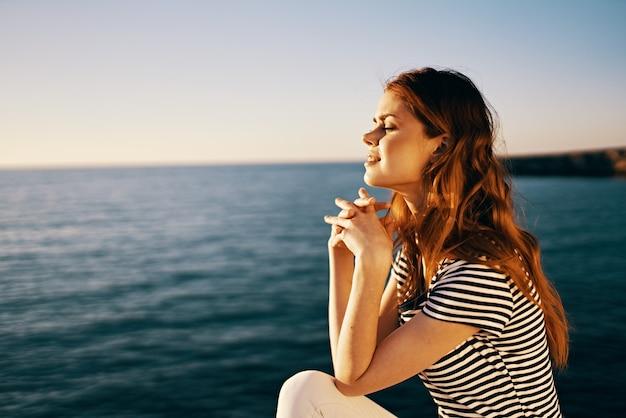 海の肖像画の側面図の近くの石の上に座って日没時の旅行者