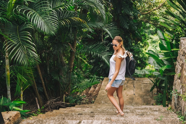 Traveler blonde backpacker woman  walking and discovering jungle tropical park, travel adventure nature in china, tourist beautiful destination asia, summer holiday vacation journey trip concept