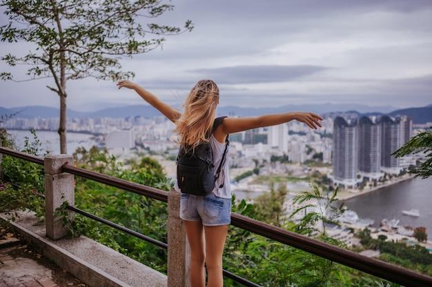 시내를 내려다 보는 여행자 금발 배낭 여자. 중국의 여행 모험, 아름다운 여행지 아시아, 여름 휴가 휴가 여행. 자유와 행복 한 사람들 개념