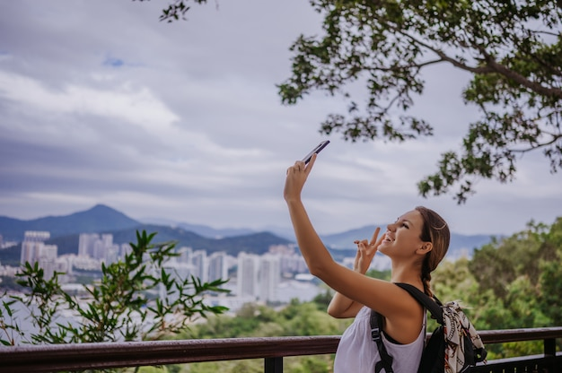 Traveler blonde backpacker woman walking taking photos from observation deck overlooking the downtown. travel adventure in china, tourist beautiful destination asia, summer holiday vacation trip