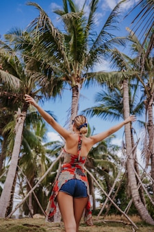 Traveler blonde beautiful woman open arms walking in jungle tropical park. travel adventure nature in china, tourist beautiful destination asia, summer holiday vacation journey trip freedom concept