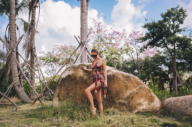 Traveler blonde beautiful woman in sunglasses walking in jungle tropical park. travel adventure nature in china, tourist beautiful destination asia, summer holiday vacation journey trip concept