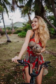 Traveler blonde beautiful woman with coconut riding a bicycle in jungle tropical park.travel adventure nature in china, tourist beautiful destination asia, summer holiday vacation journey trip concept