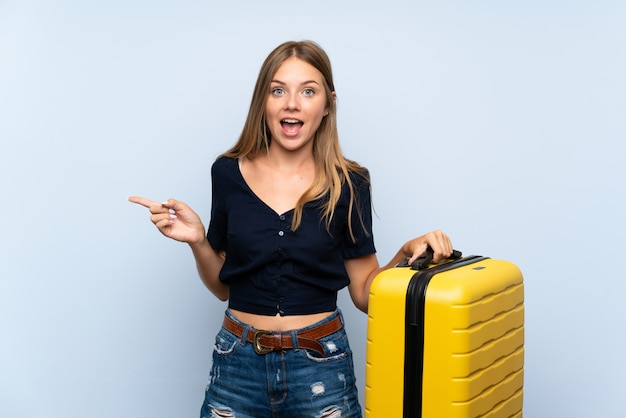 Traveler blonde woman with suitcase surprised and pointing finger to the side