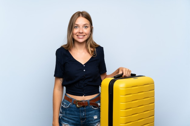 Traveler blonde woman with suitcase with surprise and shocked facial expression