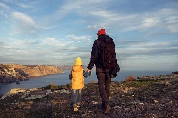아버지를 둔 여행자 소년 아이는 일몰을 등지고 재킷을 입고 바다 절벽 위를 걷는다