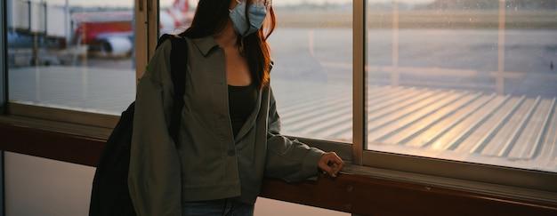 비행기를 바라보는 얼굴 마스크를 쓴 여행자 비즈니스 여성, 공항 출발 터미널에 배낭을 메고 서 있습니다. covid19 바이러스 전염병 동안 비행기로 여행하는 여성 승객.