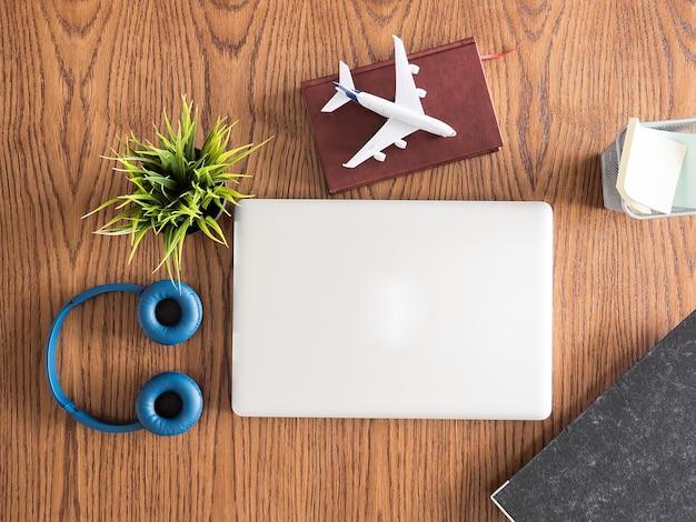 Vista dall'alto dell'uomo d'affari viaggiatore sull'immagine del concetto di scrivania in legno, cuffie, vaso d'erba, libro