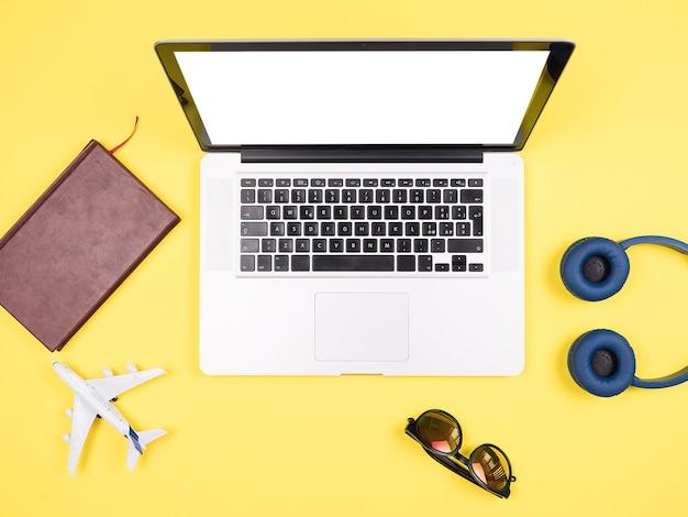 Traveler businessman top view yellow desk concept image,sunglasses, headpphones, pot of grass