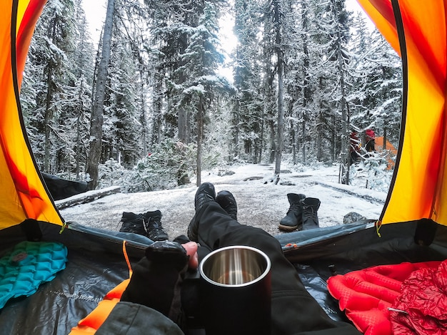 Traveler camping with hand holding cup in a tent on snow in pine forest