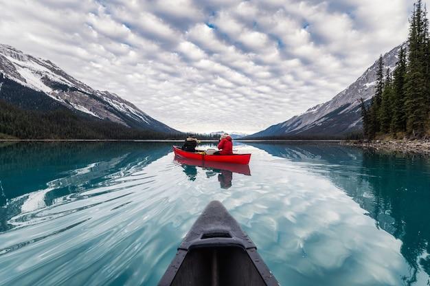 Путешественник на каноэ на озере малинь с отражением канадских скалистых гор на острове спирит в национальном парке джаспер, канада