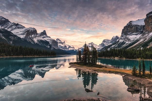 カナダ、ジャスパー国立公園のスピリット島にあるマリン湖でロッキー山脈の反射を伴う旅行者のカヌー