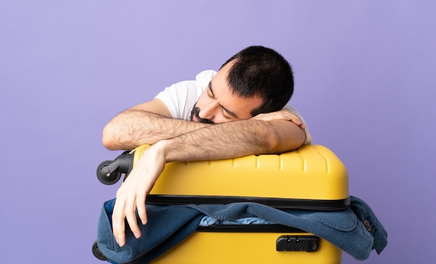Путешественник кавказский мужчина с чемоданом, полным одежды на изолированном фиолетовом