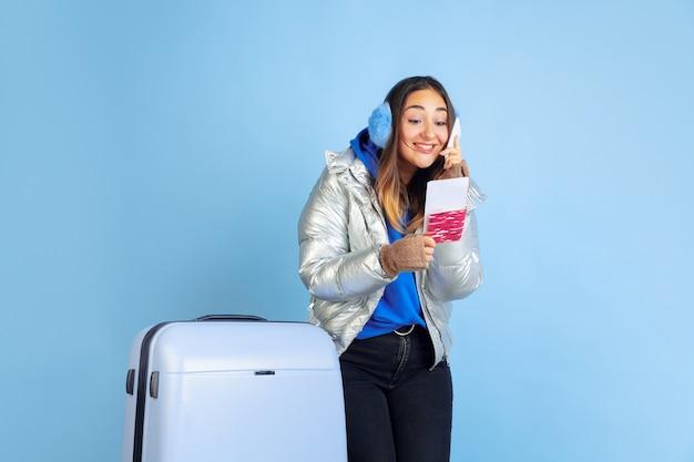 Viaggiatore. ritratto della donna caucasica su sfondo blu studio. bello modello femminile in vestiti caldi. concetto di emozioni umane, espressione facciale, vendite, annuncio. atmosfera invernale, periodo natalizio, vacanze.