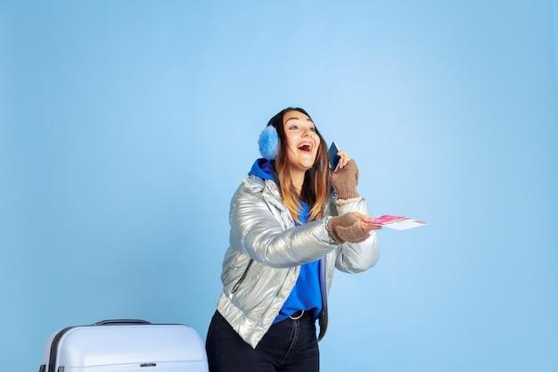 Путешественница. портрет кавказской женщины на синем фоне студии. красивая женская модель в теплой одежде. концепция человеческих эмоций, выражения лица, продаж, рекламы. зимнее настроение, рождество, праздники.