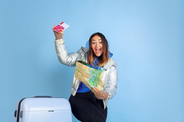 Путешественник. портрет кавказской женщины на синем фоне студии. красивая женская модель в теплой одежде. понятие человеческих эмоций, выражения лица, продаж, рекламы. зимнее настроение, рождество, праздники.