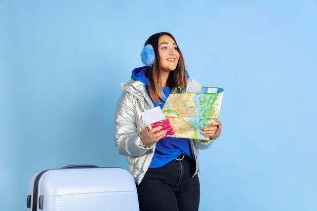 トラベラー。青いスタジオの背景に白人女性の肖像画。暖かい服を着た美しい女性モデル。人間の感情、顔の表情、販売、広告の概念。冬の気分、クリスマスの時期、休日。