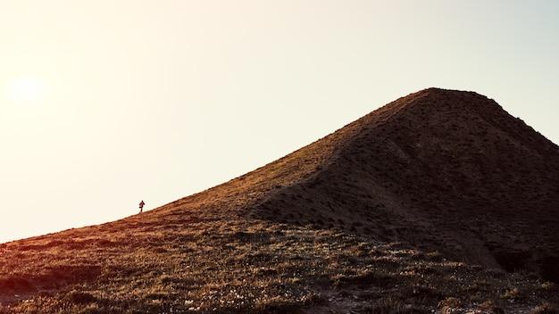 A traveler climbs a mountain