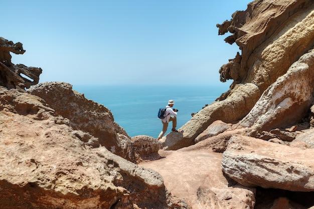 여행자는이란의 hormozgan에있는 persian gulf의 iranes hormuz 섬인 아름다운 자연의 모습을 사진을 찍기 위해 바위 위로 올라갑니다.