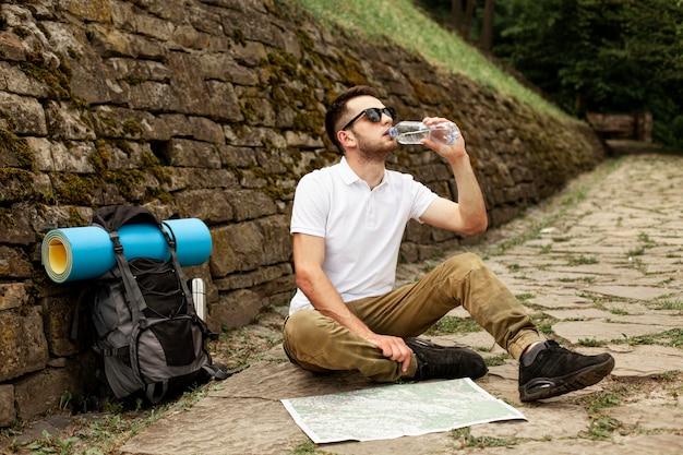 Traveler consulting map while hydrating