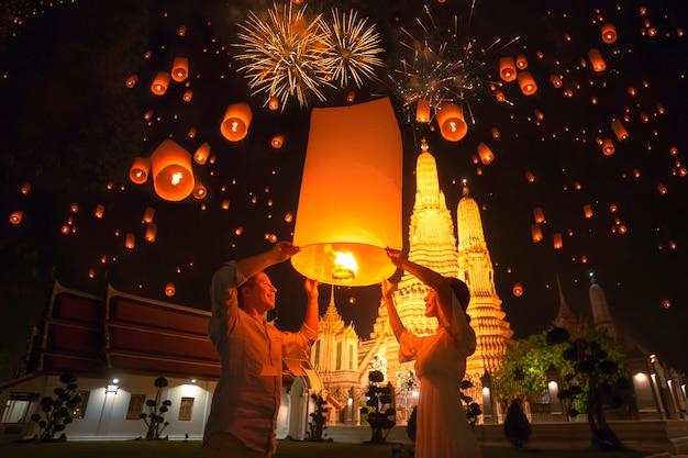 Traveler couple enjoy yeepeng floating lantern in loi kratong festival at arun temple
