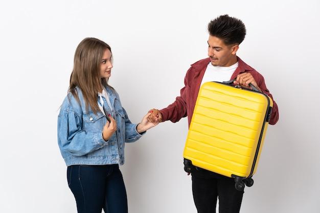 좋은 거래 후 블루 핸드 쉐이킹에 가방을 들고 여행자 커플