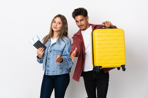 좋은 거래를 닫는 파란색 악수에 가방을 들고 여행자 커플