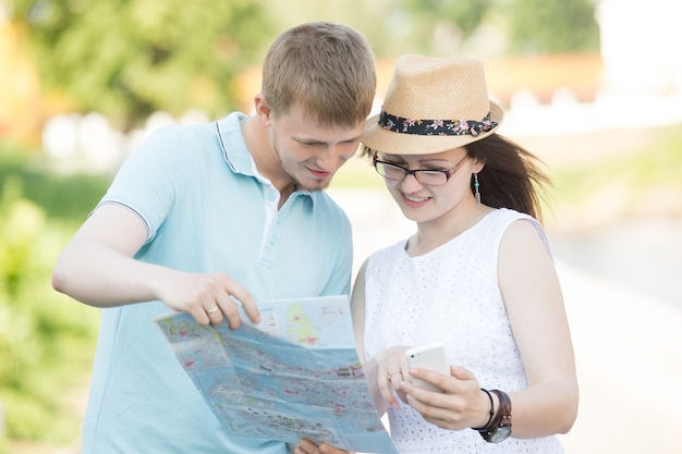 Traveler couple looking at map and phone for direction