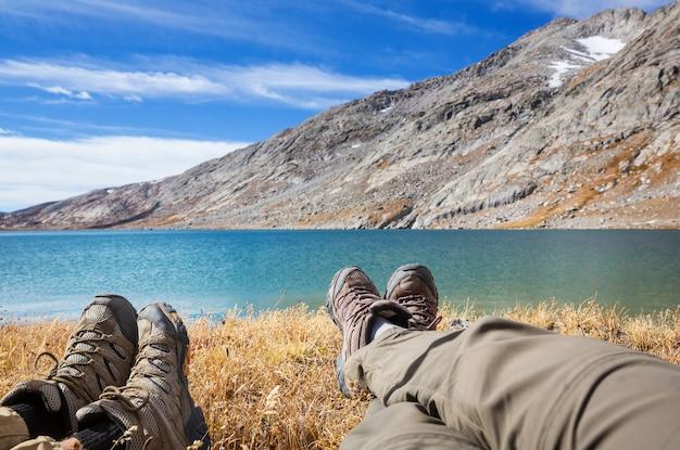 山の湖の近くでハイキングした後、リラックスした旅行者のカップル。