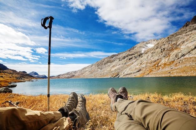 Пара путешественников, расслабляющаяся после пеших прогулок возле горного озера.