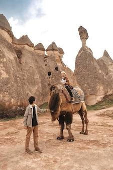 Traveler couple with camel at goreme fairy chimneys , cappadocia. nevsehir province. turkey.